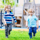 Two little sibling kid boys playing together on a playground, ou Stock Photography