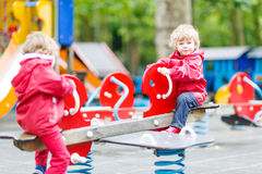 Two little sibling kid boys playing together on a playground, ou Stock Photo