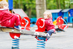Two little sibling kid boys playing together on a playground, ou Stock Image