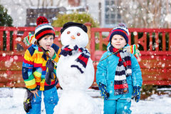 Two little siblings boys making a snowman Royalty Free Stock Photo
