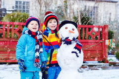 Two little siblings boys making a snowman in Stock Image