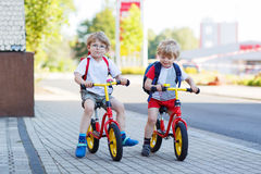 Two little siblings children having fun on bikes in city, outdoo. Two little boys having fun on bikes in city on vacations, outdoors Royalty Free Stock Photos