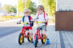 Two little siblings children having fun on bikes in city, outdoo Stock Photo
