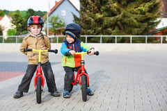 Two little siblings having fun on bikes in city on vacations Royalty Free Stock Image