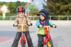 Two little siblings having fun on bikes in city on vacations Stock Photo