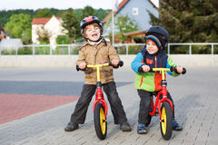 Two little siblings having fun on bikes in city on vacations Stock Photos