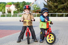 Two little siblings having fun on bikes in city on vacations Stock Photography