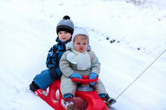 Two little siblings having fun on sledge Royalty Free Stock Photo
