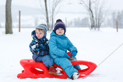 Two little siblings having fun on sledge on winter snow day Stock Photos