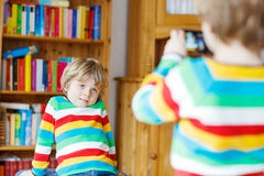 Two little siblings kid boys  making photos with photocamera, in Royalty Free Stock Photos