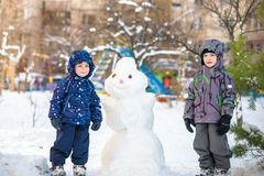 Two little siblings kids boys making a snowman, playing and having fun with snow, outdoors on cold day. Active leisure children in Royalty Free Stock Images