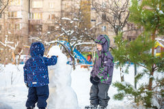 Two little siblings kids boys making a snowman, playing and having fun with snow, outdoors on cold day. Active leisure children in Royalty Free Stock Photos