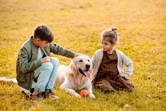 Two little siblings petting a dog and sitting on grass royalty free stock photo
