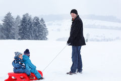 Two little siblings and their father having fun on sledge on win Stock Images