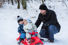 Two little siblings and their father having fun on sledge. On winter snow day Royalty Free Stock Photography