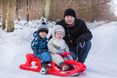 Two little siblings and their father having fun on sledge. On winter snow day Stock Images