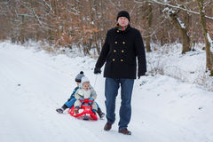 Two little siblings and their father having fun on sledge. On winter snow day Royalty Free Stock Photo