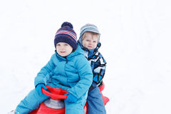 Two little siblings and their mother having fun on sledge on win Stock Images