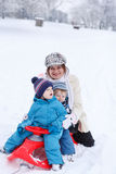 Two little siblings and their mother having fun on sledge on win Royalty Free Stock Images