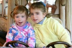 Two little sister girls driving car on fairground Royalty Free Stock Photo