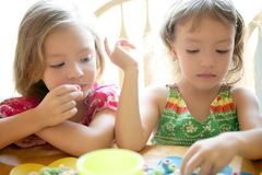 Two little sister girls eating together stock images