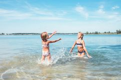 Two little sister girls fooling around in the calm sea waves splashing water to each other. Family vacation concept image royalty free stock photos