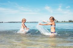 Two little sister girls fooling around in the calm sea waves splashing water to each other. Family vacation concept image stock image