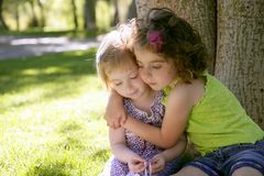 Two little sister girls hug playing under tree royalty free stock images