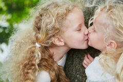 Two little sister girls kissing Royalty Free Stock Photography