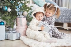Two little sister girls open their gifts at the Christmas tree in the morning on the deck Royalty Free Stock Photo