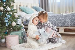 Two little sister girls open their gifts at the Christmas tree in the morning on the deck Stock Image