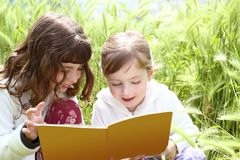 Two little sister girls reading book spikes garden Royalty Free Stock Images