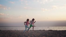 Two little sister girls running around on the beach at sunset. Happy carefree childhood stock video