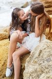 Two little sister girls sitting on the beach Royalty Free Stock Photography