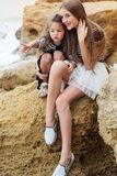 Two little sister girls sitting on the beach Royalty Free Stock Photos