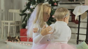 Two little sister near decorated christmas tree. Older sister hugging younger stock footage