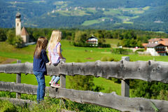 Two little sisters admiring beautiful landscape in Dolomites mountain range, South Tyrol province of Italy Stock Photos