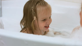Two little sisters bathing in a bathtub with foam Stock Image
