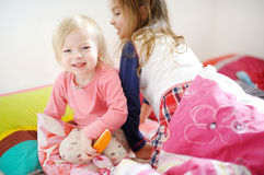 Two little sisters in bed on sunny morning Royalty Free Stock Photography