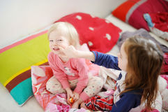 Two little sisters in bed on sunny morning Stock Images