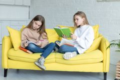 Two little sisters in casual clothes sitting together on yellow sofa royalty free stock image