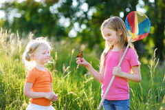 Two little sisters catching butterflies and bugs with their scoop-nets Royalty Free Stock Photography