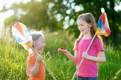 Two little sisters catching butterflies and bugs with their scoop-nets Royalty Free Stock Image