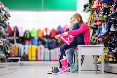 Two little sisters choosing and trying on new rain boots Royalty Free Stock Photos