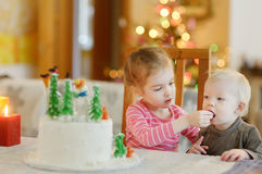 Two little sisters and a Christmas cake Royalty Free Stock Images
