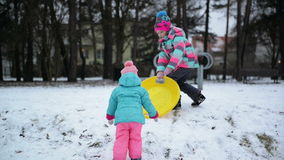 Two Little Sisters in Colorful Clothes Enjoying Snowy Weather and Sledge are Trying to Climb up the Hill. Funny Girls stock video