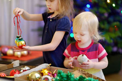 Two little sisters decorating a Christmas tree. Two adorable little sisters decorating a Christmas tree with colorful glass baubles at home Royalty Free Stock Photos
