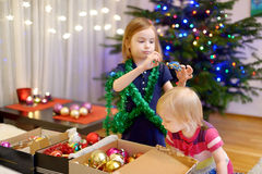 Two little sisters decorating a Christmas tree Stock Images
