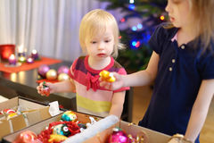 Two little sisters decorating a Christmas tree Stock Image