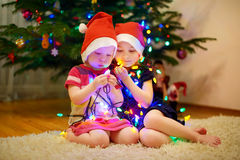 Two little sisters decorating a Christmas tree. Two adorable little sisters decorating a Christmas tree at home Royalty Free Stock Image